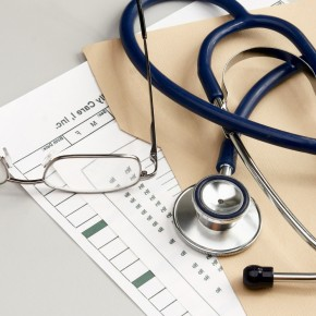 glasses and stethoscope on independent medical examination paperwork on the desk of a toledo insurance attorney