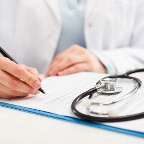 doctor looking at medical bills provided by toledo insurance claims attorneys