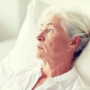 Lonely elderly woman looking off in the distance as she lays in bed, and if you suspect nursing home abuse call a Toledo Nursing Home Negligence Attorney.