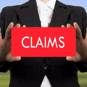 Man holding a card that says Claims, and if you have a premises claim call a Toledo Premises Liability Lawyer.