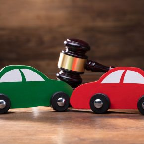 Collision of two wooden car in front of gavel and if you need a good car accident attorney, find one in Maumee.