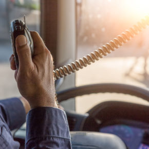 Truck Driver Talking on Walkie slightly impaired, if injured from a semi truck, consult with a Maumee Truck Accident Lawyer