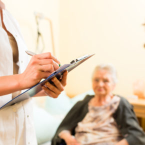 Female senior in nursing home with nurse representing how our Toledo nursing home abuse lawyer can help your loved one