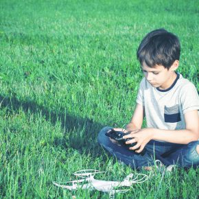 Boy sitting in grass trying to play with his drone, if your child was injured from a defective toy speak with Product Liability Lawyers Toledo.
