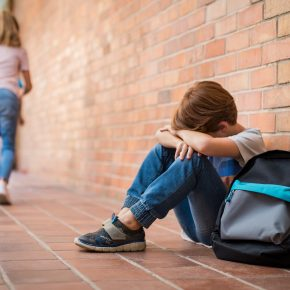 A boy sitting down in hallway at school after being victim of bullying. When deciding to apply premises liability lawsuit meet with our skilled Ohio Personal Injury Attorney.