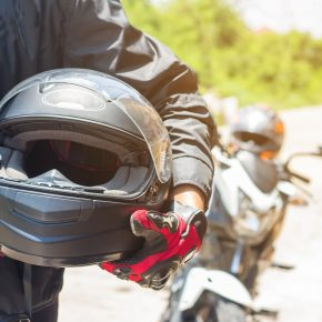A motorcyclist holding his helmet with motorcycle behind him, an experienced Toledo Motorcycle Accident Attorney can assist with your accident claim.