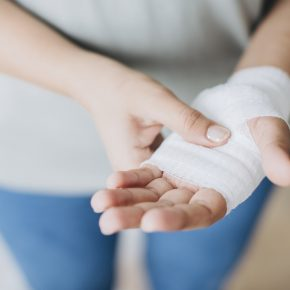 Woman with bandage on her hand, our Defective Product Claim Lawyer can help you file lawsuit.