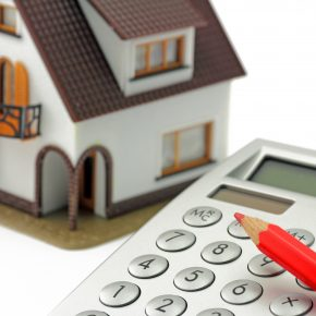 A small model of a house, calculator, and red pencil on a white background representing how a Findlay premises liability attorney may be able to help your case.